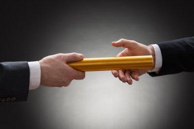 Hands Passing Golden Relay Baton