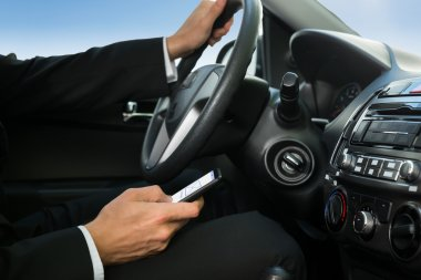 Man Texting While Driving Car