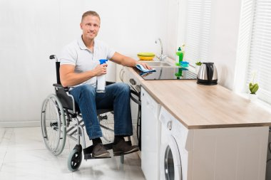 Man On Wheelchair Cleaning Stove