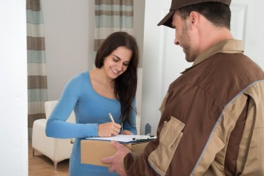 Woman Signing While Receiving parcel
