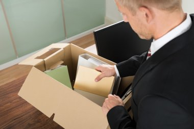 Businessman Packing Files In Cardboard Box
