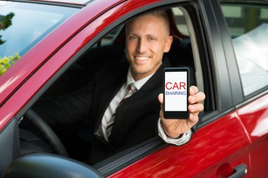 Businessman Showing Cellphone in Car