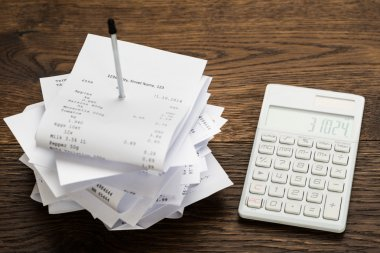 Receipts With Calculator On Table