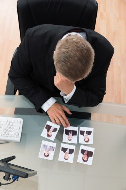 Businessman Looking At Candidates Photographs