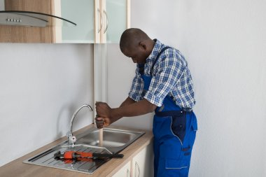 Plumber Cleaning Sink