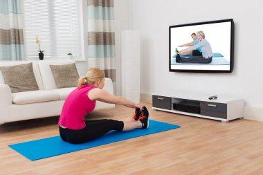 Woman Exercising While Watching Program