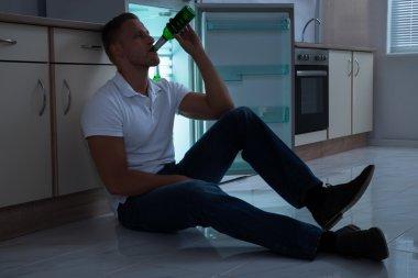Man Drinking Beer In Kitchen