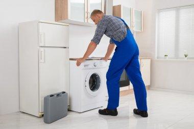 Worker Repairing Washer