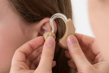Doctor Inserting Hearing Aid In The Ear Of A Girl