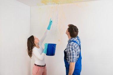 Woman Showing Water Leaking To Maintenance Guy