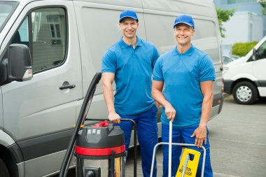 Cleaners Standing With Cleaning Equipments