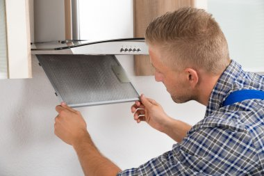Repairman Repairing Kitchen Extractor Filter