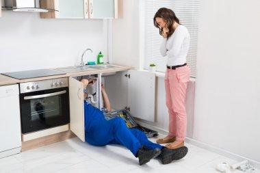 Repairman Repairing Pipe While Woman Standing