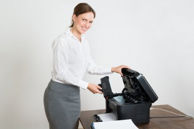 Businesswoman Holding Laser Cartridge With Printer