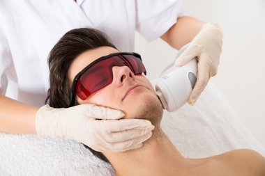 Beautician Giving Laser Epilation Treatment To Face