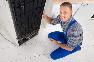 Repairman Repairing Fridge