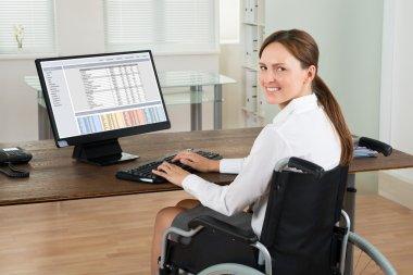 Businesswoman On Wheelchair Using Computer
