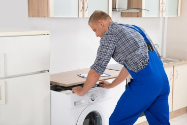 Worker Repairing Washer