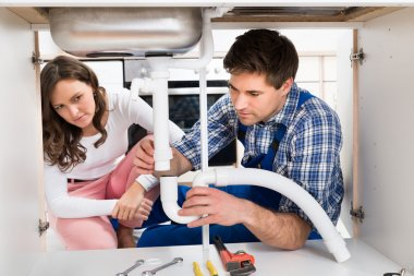 Woman Looking At Worker Fixing Pipe
