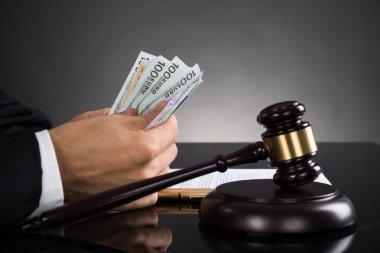 Judge Counting Banknotes At Desk