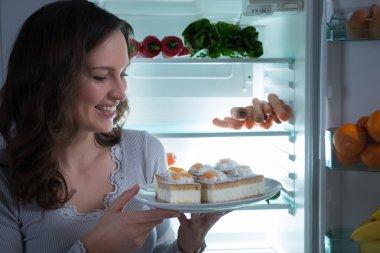 Woman Eating Cake Near The Fridge