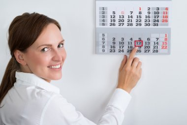 Businesswoman Placing Red Mark On Calendar