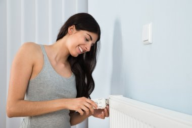 Woman Adjusting Thermostat On Radiator