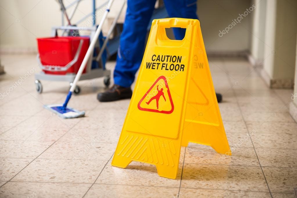 Lavoratore straccio pavimento con segno di attenzione pavimento