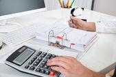 Geschäftsmann berechnet Budget am Schreibtisch