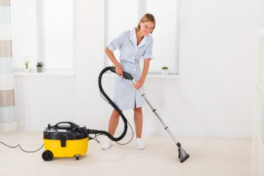 Female Maid Vacuuming Floor