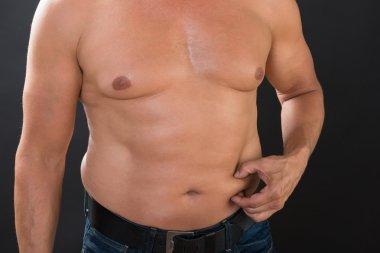 Shirtless Man Measuring Stomach Fat