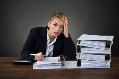 Stressed Businesswoman Looking At Folders