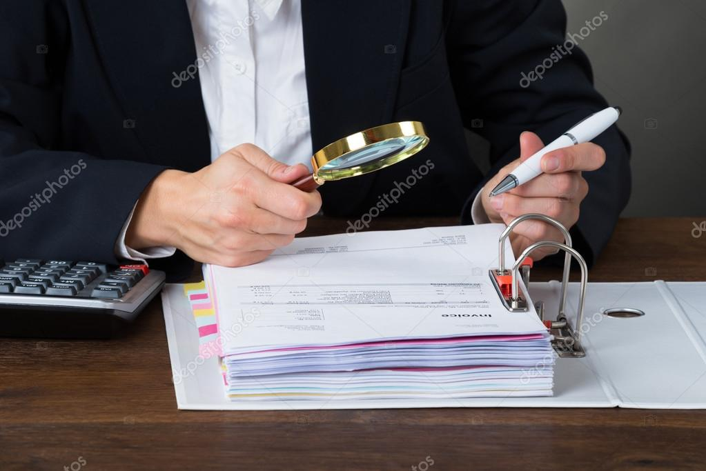 Accountant Scrutinizing Bills With Magnifying Glass