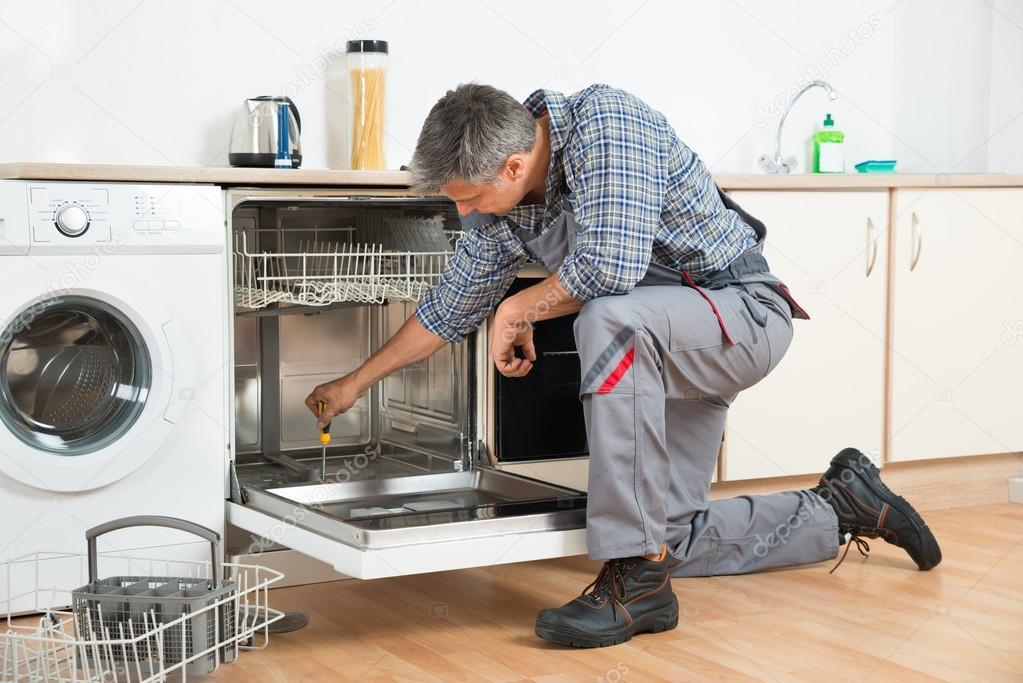 Reparateur herstellen vaatwasser met schroevendraaier in keuken