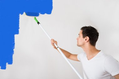 Man Painting Wall With Blue Paint