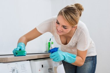 Woman Cleaning Kitchen Counter With Sponge