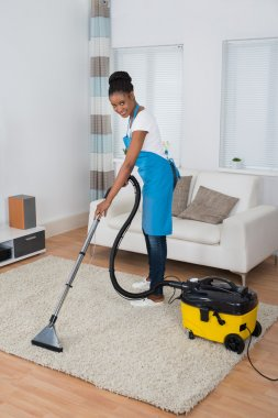 Woman Cleaning Carpet With Vacuum Cleaner