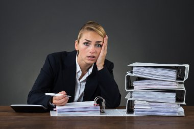 Stressed Businesswoman Working At Desk