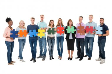 Full length portrait of creative business people holding jigsaw pieces against white background stock vector