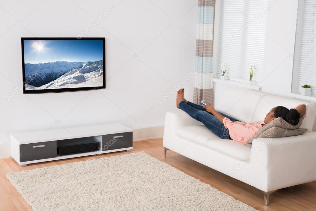 Afrikanische Frau liegend auf dem Sofa vor dem Fernseher — Stockfoto ...