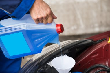 Pouring Windshield Washer Fluid Into Car