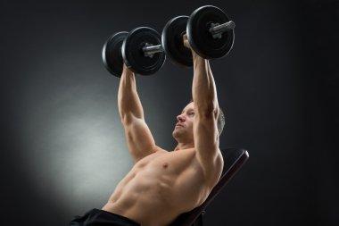 Determined Man Lifting Dumbbells
