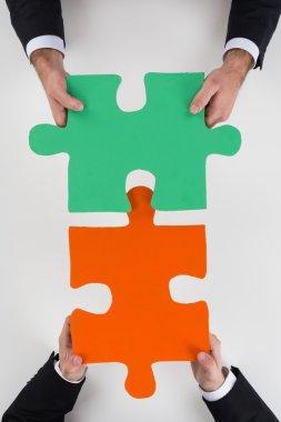 Businessmen Assembling Jigsaw Puzzle