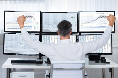 Successful Trader  Looking At Graphs On Screens