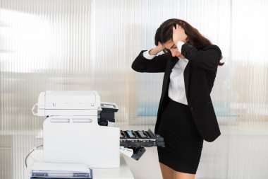 Irritated Businesswoman Looking At Printer