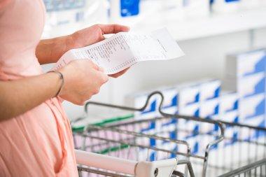 Woman Holding Receipt In Supermarket