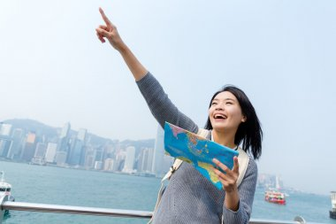 Woman looking far away and holding map