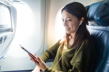 woman listening to music in airplane