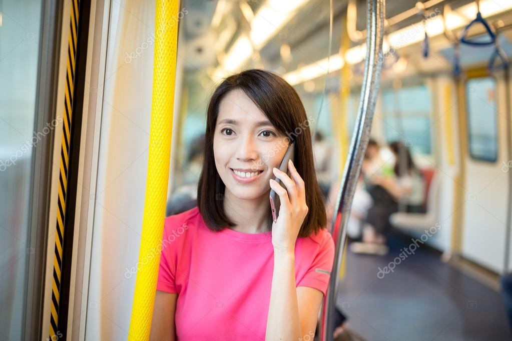 woman talking on cellphone inside train