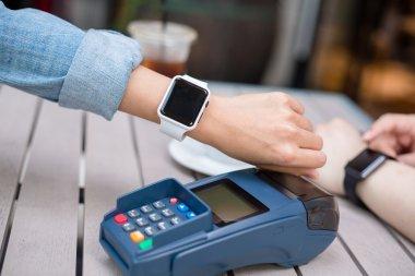 Woman wearing smart watch on pos terminal